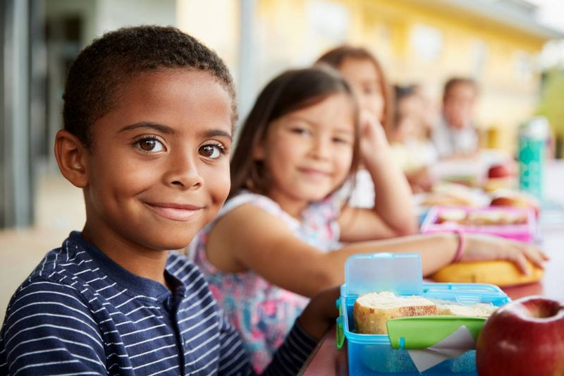 smiling child eating lunch at school in Canada | immigrate to Canada