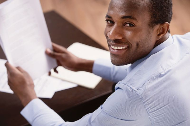 smiling man filling out documents