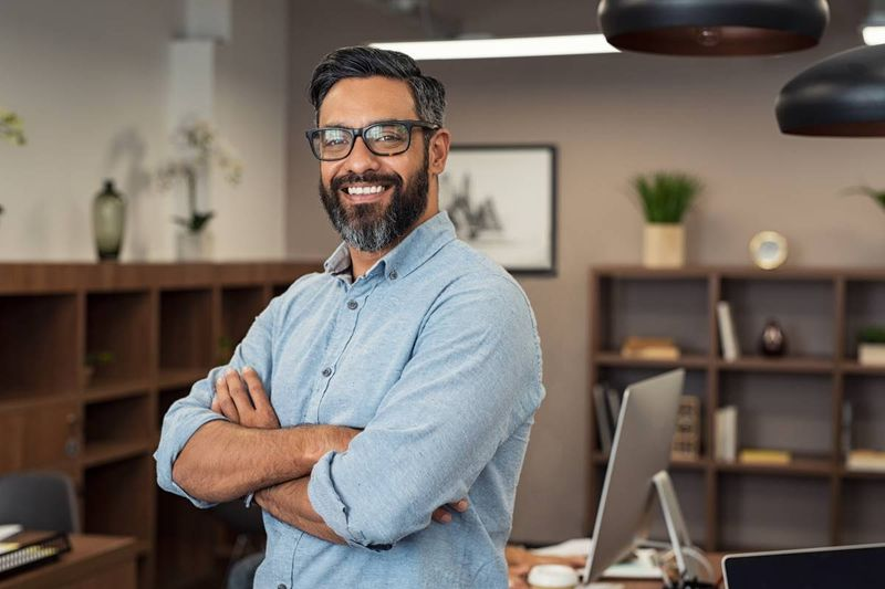 smiling multiethnic man with arms crossed in office | work in Canada