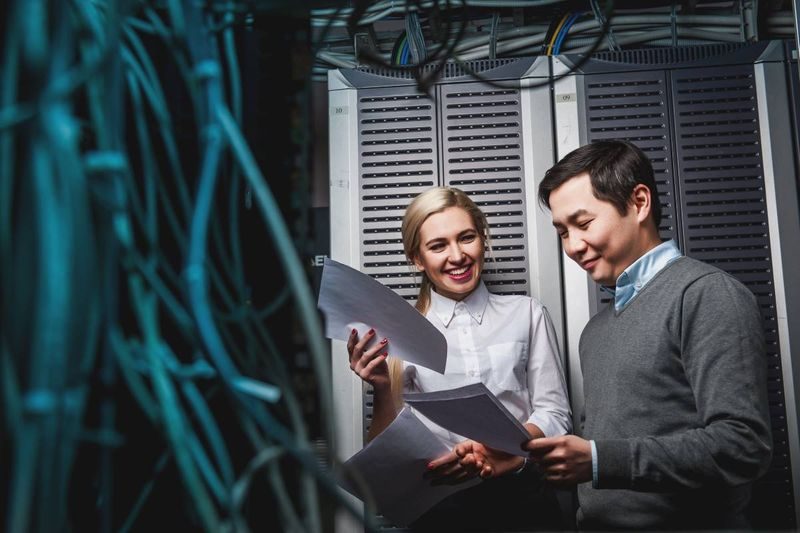 smiling tech workers in server room | how to immigrate to Canada