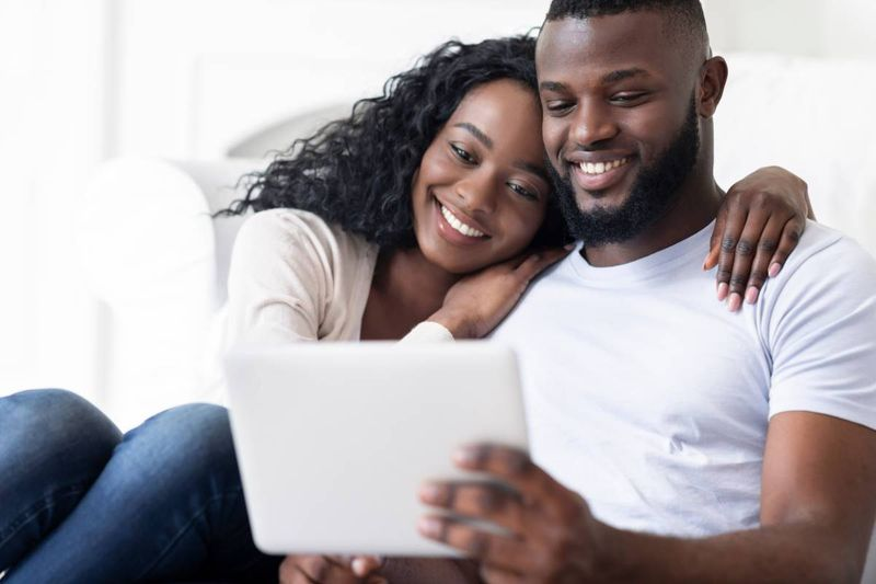 happy African couple applying for Canada visa from Uganda on ipad