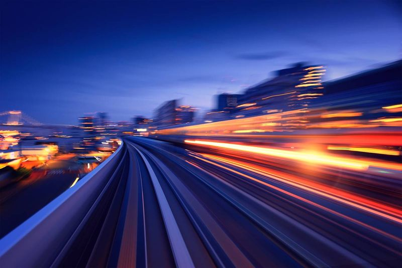 speeding train blurred lights at night in city   immigrate to Canada