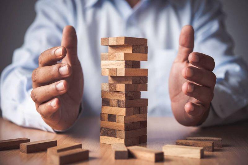 stability businessman risk assessment jenga wooden blocks | Canadian permanent residence
