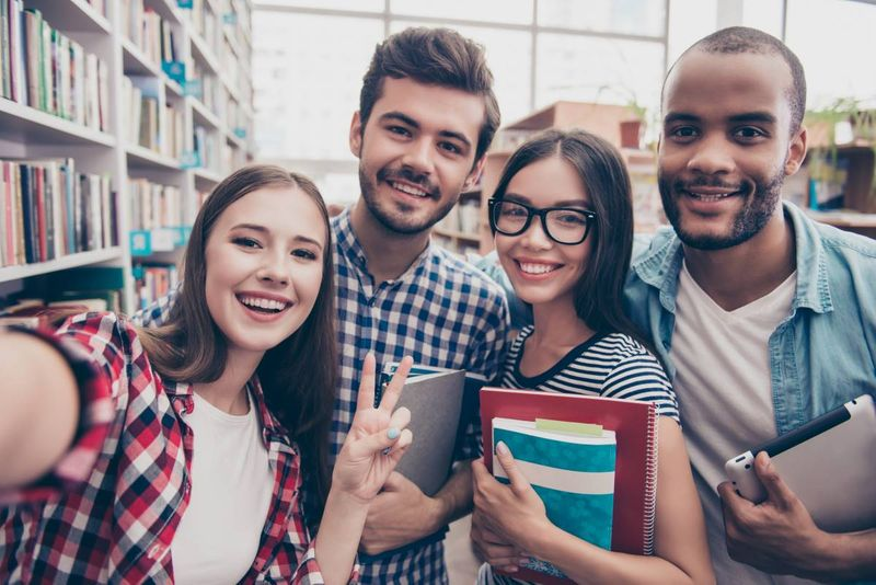 students taking a selfie in library on campus | study in Canada visa