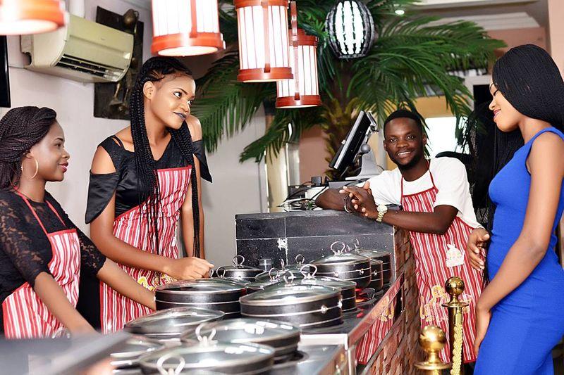 3 Jamiacan women and man in aprons in Canadian Caribbean restaurant