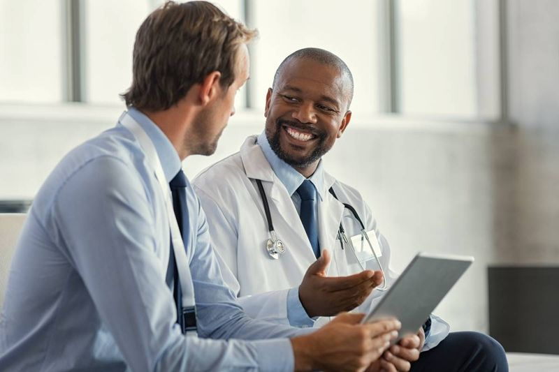 Two-male-doctors-smiling-discussing-patient-file-on-tablet | work in Canada