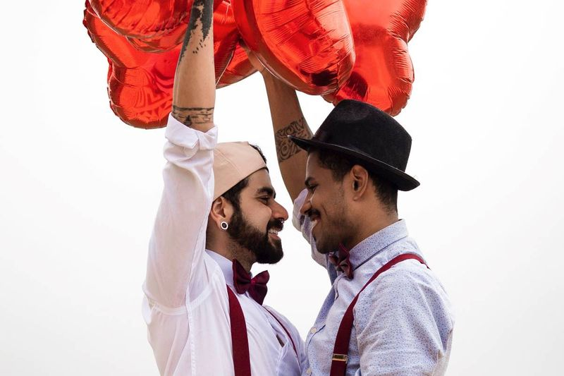 two men holding red heart balloons in love