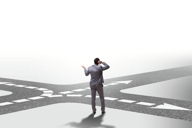 unsure businessman standing at a crossroad | immigrate to Canada