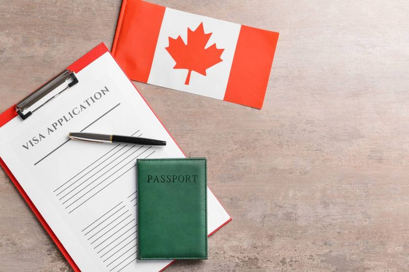 visa application form Canadian flag and green passport   Canadian permanent residency