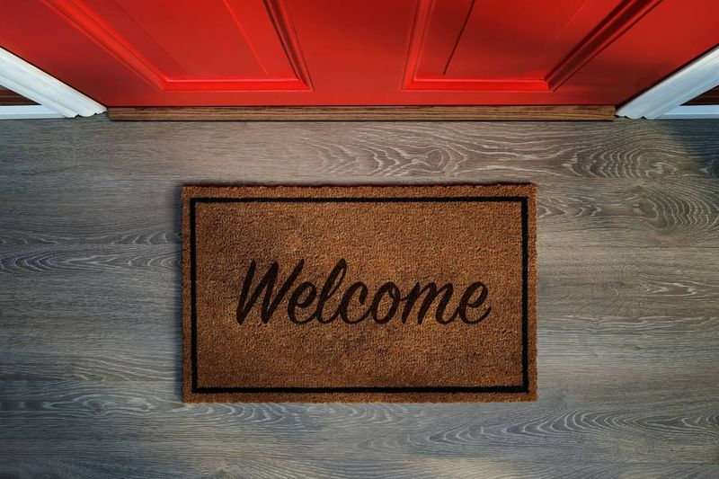 welcome mat outside red front door | move to canada