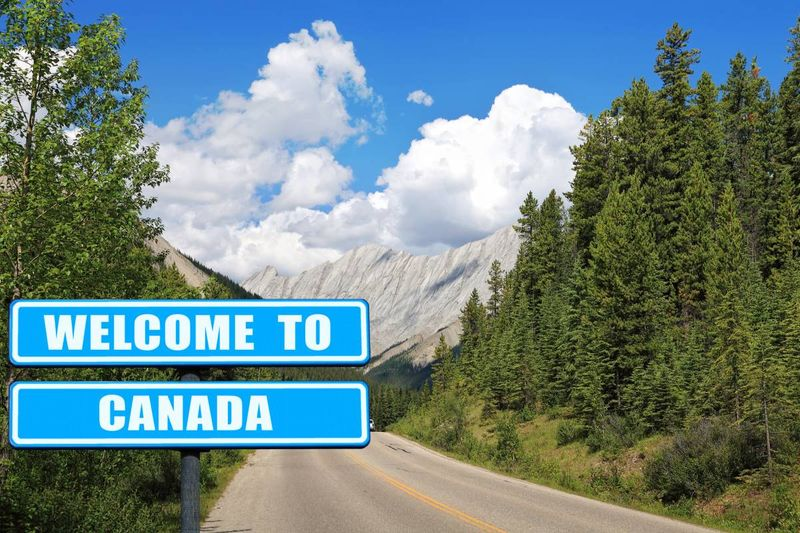 welcome to Canada sign trees mountains