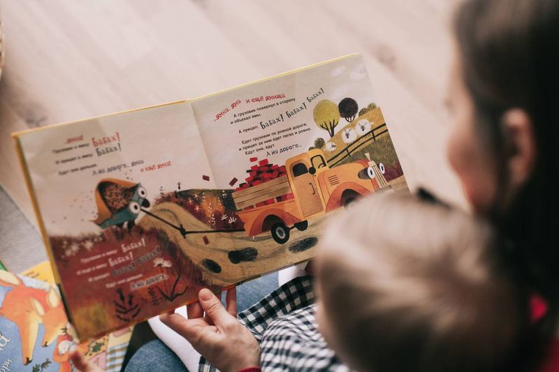 female child-care worker reading a book to a Canadian child   work in canada