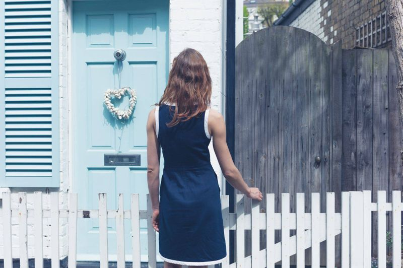 Woman looking at a blue door house in Canada, finding accommodation in Canada