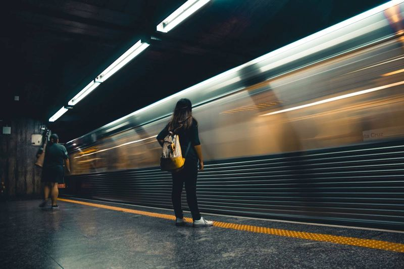woman standing in front of speeding train | Express Entry to permanent residence in Canada