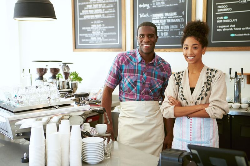 young business owners standing in their cafe